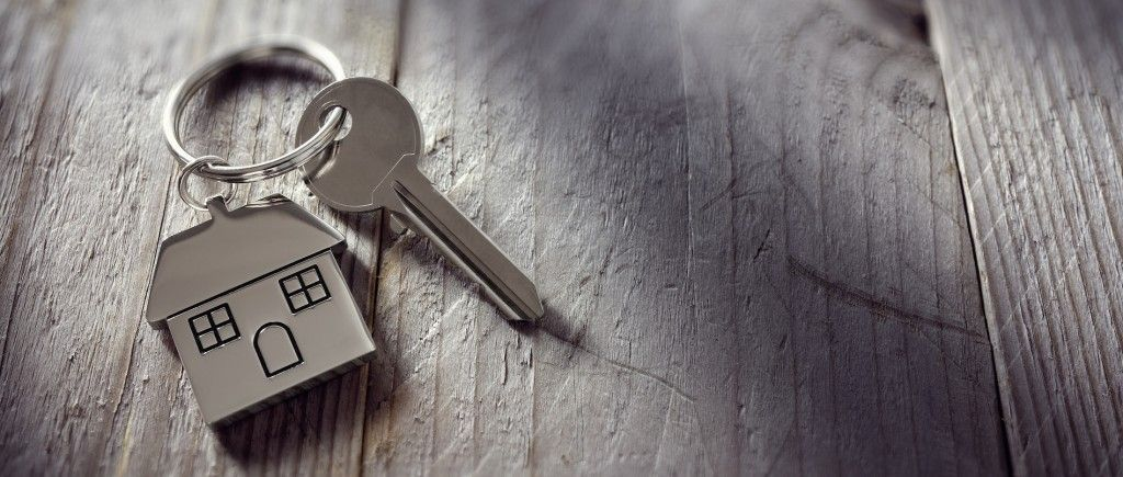 House key on a house shaped keychain resting on wooden floorboards concept for real estate, moving h