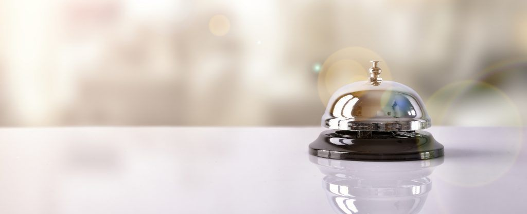 Hotel service bell on a table white glass and simulation hotel background. Concept hotel travel room