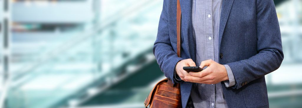Young urban professional man using smart phone in office building indoors. Businessman holding mobil