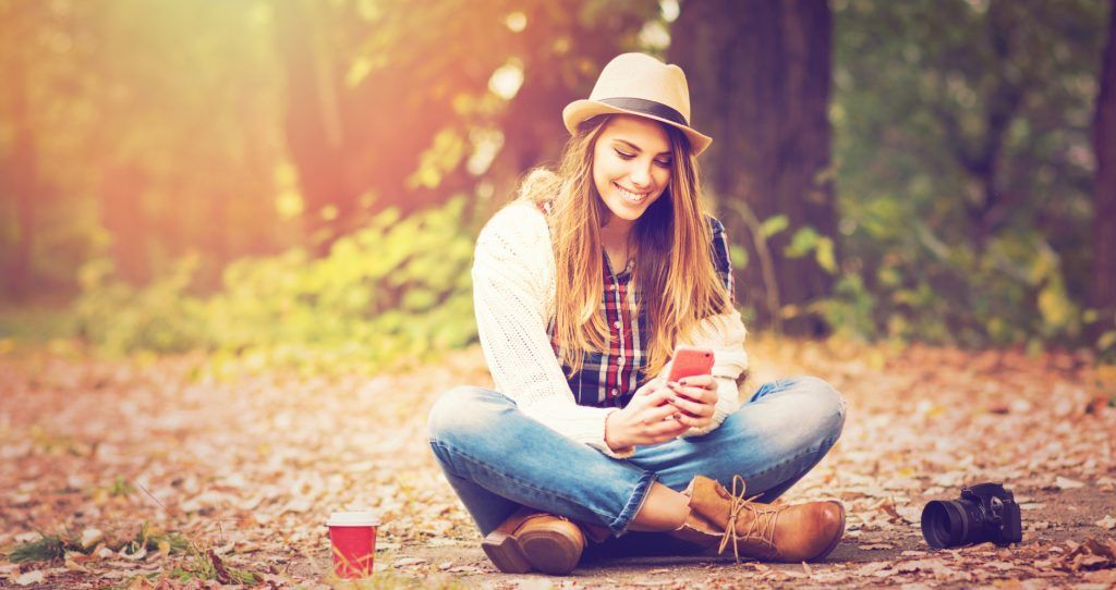 Young woman with smartphone, camera and coffe in park in autumn