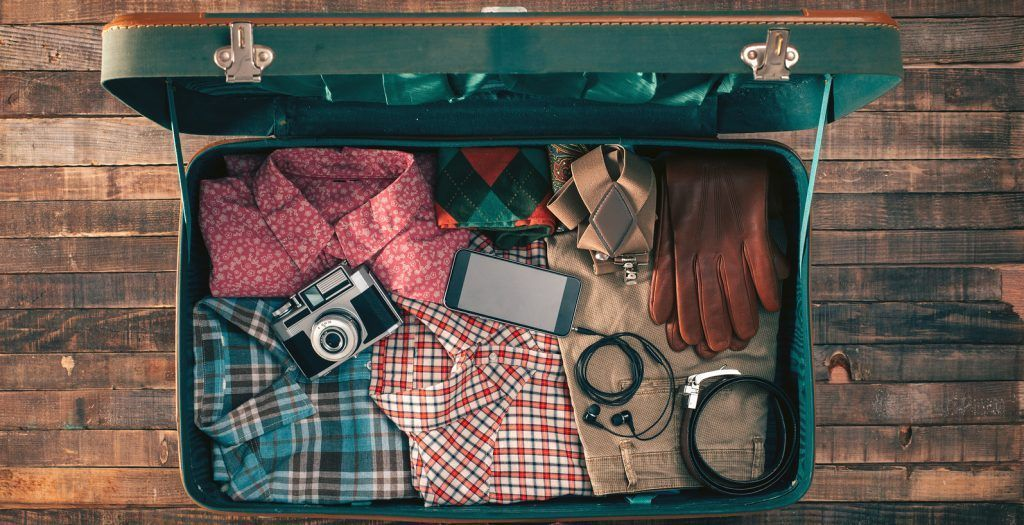 Vintage hipster traveler packing open suitcase on a wooden table with clothing camera and mobile phone top view
