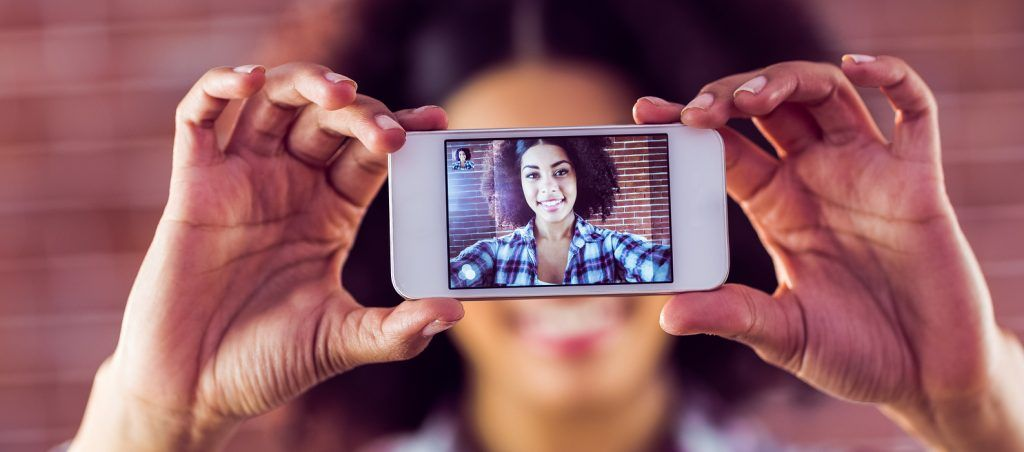 Attractive young woman taking selfies with smartphone against red brick background