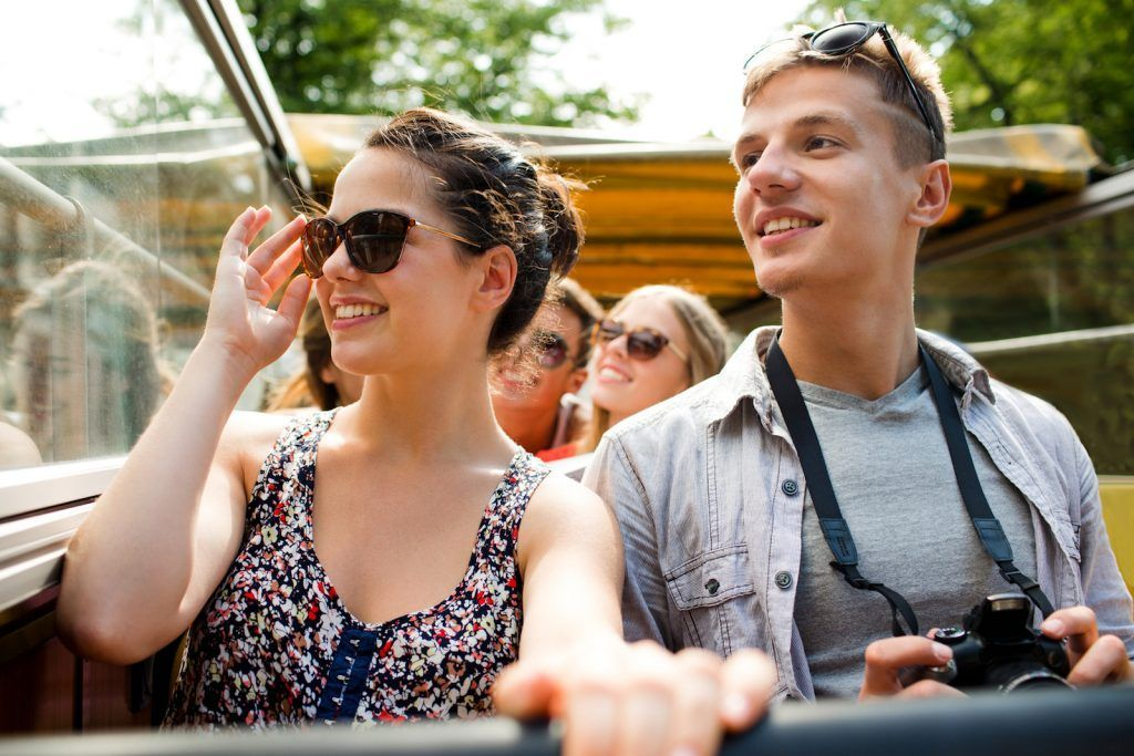 smiling couple with camera traveling by tour bus