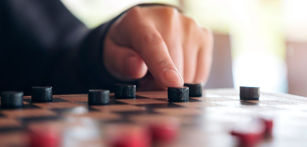 Closeup Image Of People Playing And Moving Checkers In A Chessbo