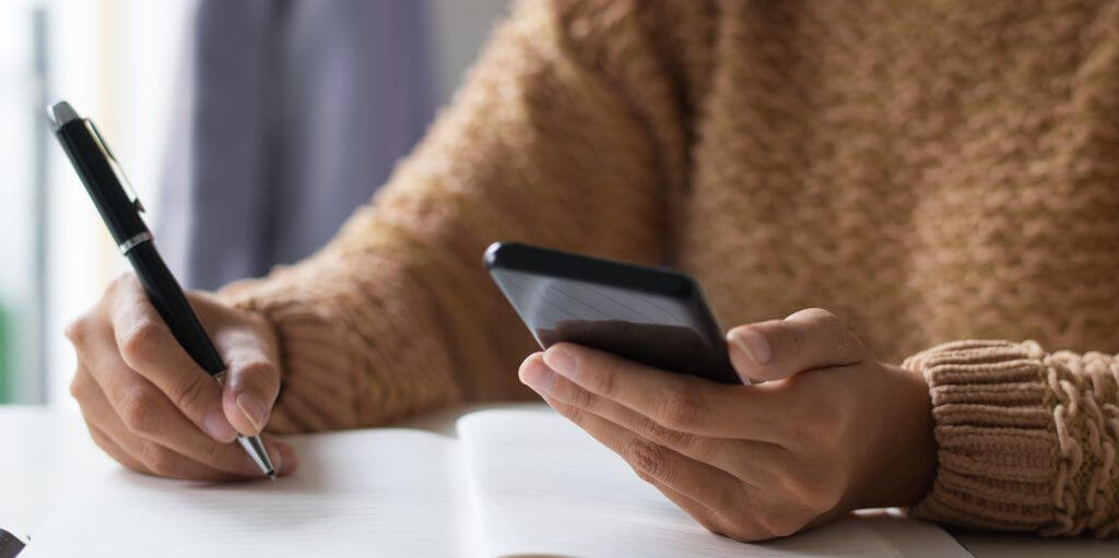 Close-up of businesswoman planning timetable using smartphone. Unrecognizable lady sitting at table and making notes in organizer. Schedule concept