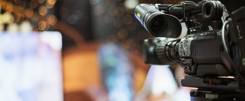 Video camera taking live video streaming with people working background at meeting room. Selective focus.