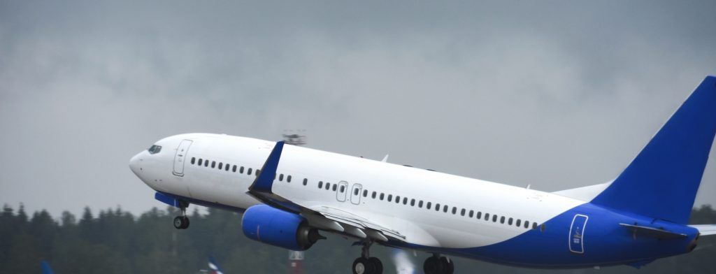 Passenger liner takes off into sky from the airport runway in cloudy weather with rain