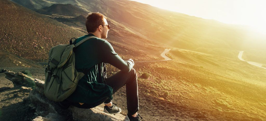 Man with rucksack sitting on rock at sunset on background of volcano Etna mountain in Sicily