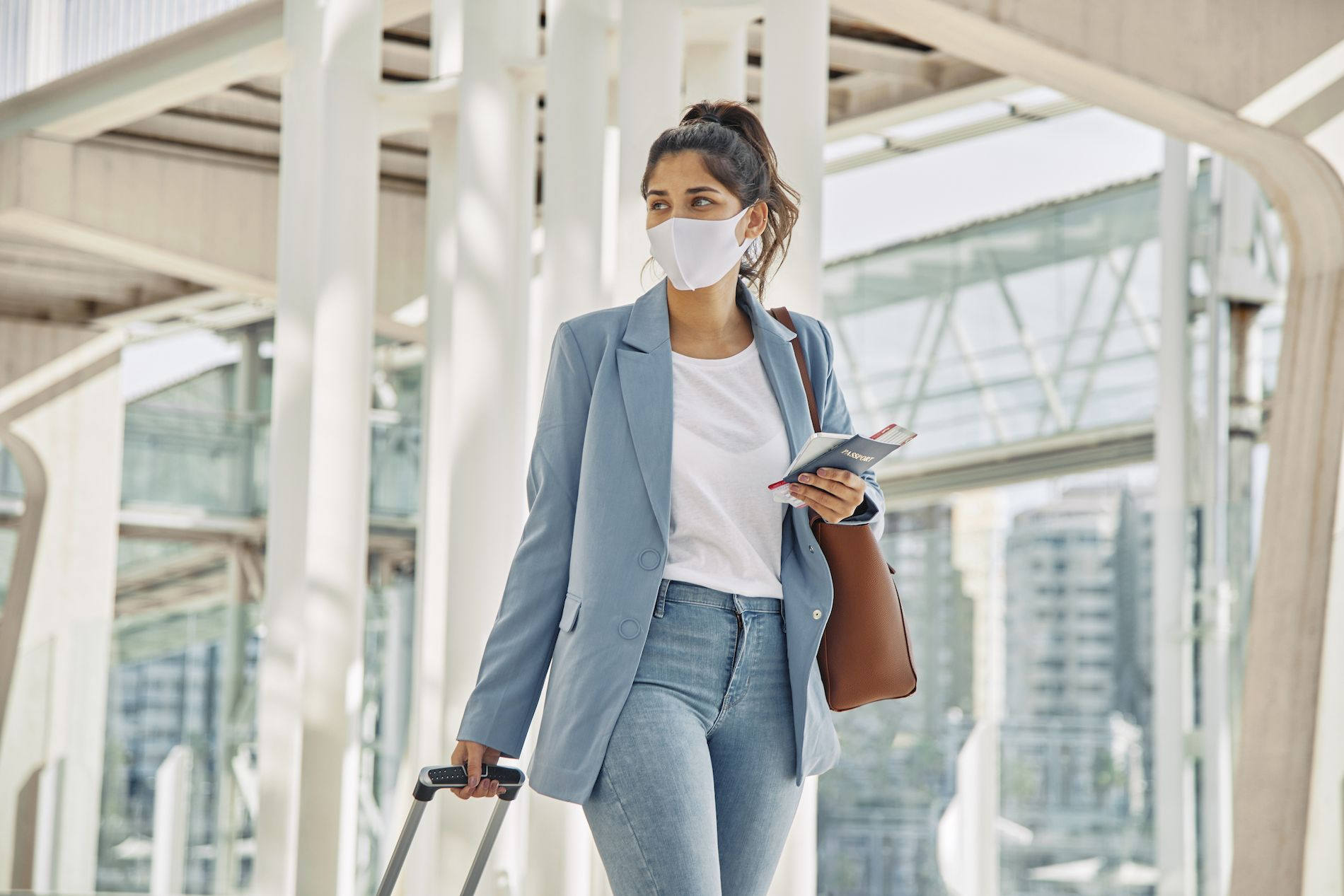woman-with-luggage-and-medical-mask-at-the-airport-during-pandemic.jpg